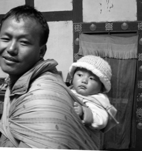 "Infant being carried in traditional Bhutanese ""kamnay"" by her father"